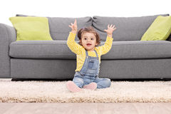 Playful baby girl gesturing happiness seated on floor. Studio shot of a playful baby girl sitting on the floor next to a modern sofa and gesturing happiness Royalty Free Stock Photos