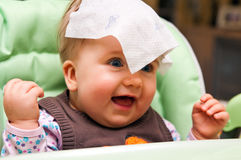 Playful baby girl portrait. Portrait of a playful baby girl with a tissue over her head Royalty Free Stock Images