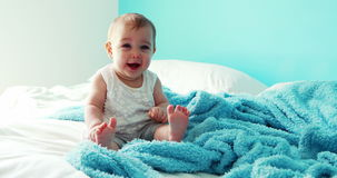 Playful baby girl sitting on bed stock footage