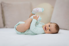 Playful baby lying down in bed. Happy baby lying on white sheet and holding her legs Royalty Free Stock Image