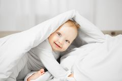 Playful baby sits on bed and hides under warm blanked. Playful baby with big light eyes, excited look and plump cheeks sits on comfortable bed and hides under Stock Images