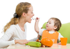 Playful baby spoon feeding his mother Royalty Free Stock Photo