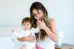 playful baby trying to comb a womans hair Stock Photography