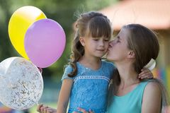 Playful beautiful blond small girl with colorful balloons in nice blue dress kissing her young mother on blurred summer royalty free stock photo