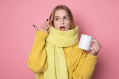 Playful beautiful blonde girl with cup in hand, wearing yellow sweater and scarf royalty free stock photos