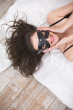Playful beautiful brunette in a black leather mask Royalty Free Stock Photography
