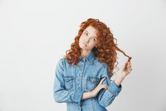 Playful beautiful girl with foxy red hair thinking dreaming biting lips over white background. Copy space Royalty Free Stock Photos