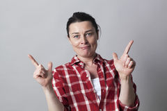 Playful beautiful middle aged woman showing hands like sexy guns Royalty Free Stock Photo