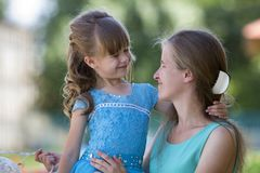 Playful beautiful small girl with long blond hair in nice blue dress hugging her mum`s neck and looking at her with smile on blur stock photography