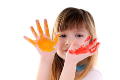 Playful beauty girl with many-coloured hands. Small playful beauty girl with many-coloured hands on white background royalty free stock photo