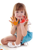Playful beauty girl with many-coloured hands. Small playful beauty girl with many-coloured hands on white background stock photo