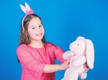 Playful beauty. Little girl with hare toy. Egg hunt. Family holiday. Happy easter. Spring party. Child in rabbit bunny. Ears. Capturing a happy moment. Ready to stock photo
