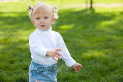 Playful blond little girl walking in the park Stock Photo