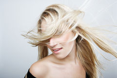Playful blond woman flicking her hair. Playful blond woman flicking her long hair so that it swirls around her face obscuring her eyes, studio head and shoulders Stock Images
