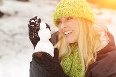 Playful Blonde Woman Making a Snowman in the Winter Outdoors Stock Photos