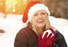 Playful Blonde Woman In Santa Hat Making Snowballs Outdoors Royalty Free Stock Image