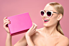 Playful blonde woman wearing sunglasses. Look what I got for you. portrait of cute young female holding pink gift box and smiling, isolated on color background Royalty Free Stock Photos
