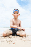 Playful boy on the beach with sea  on background. Stock Photo