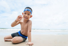 Playful boy on the beach with sea  on background. Royalty Free Stock Photos