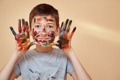 Playful boy being messy with colorful paints. Happy teenage boy with face and hands in colorful paints smiling at camera stock photography