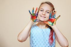 Playful boy being messy with colorful paints. Happy teenage boy with face and hands in colorful paints smiling at camera royalty free stock photo