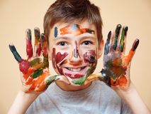 Playful boy being messy with colorful paints. Happy teenage boy with face and hands in colorful paints smiling at camera royalty free stock images