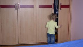 Playful boy with bunny friend hiding in wardrobe stock video