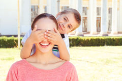 Playful boy covering eyes of his mother Royalty Free Stock Images