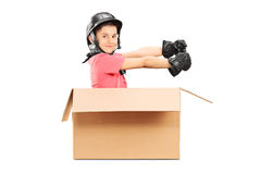Playful boy with helmet sitting in carton box Stock Image
