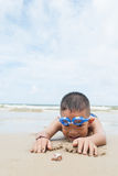 Playful boy and Hermit crab on the beach. Royalty Free Stock Images