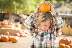 Playful Boy Holding His Pumpkin at a Pumpkin Patch. Adorable Little Boy Sitting and Holding His Pumpkin in a Rustic Ranch Setting at the Pumpkin Patch stock photography