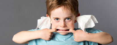 Playful boy not listening with tissue in both ears Royalty Free Stock Image