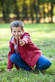 Playful boy shooting with finger at camera Royalty Free Stock Image