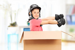Playful boy sitting in a box indoors Royalty Free Stock Photo
