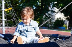 Boy sitting on a swing in the park. Playful boy sitting on a round swing in the park Stock Images