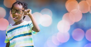 Playful boy sticking out tongue while holding eyeglasses over bokeh Royalty Free Stock Images