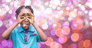 Playful boy sticking out tongue over bokeh Royalty Free Stock Photos