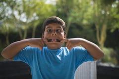Playful boy teasing at park. Playful boy teasing while standing at park Royalty Free Stock Photos