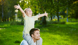Playful boys. Father and small son frolic in a summer garden Royalty Free Stock Image