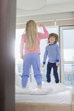 Playful brother and sister standing on bed Royalty Free Stock Photos