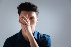 Playful brunette holding arm in front of his nose. Open your face. Attractive male person looking straight at camera and raising hand while standing isolated on Royalty Free Stock Photography
