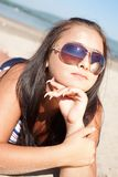 Playful brunette is lying on the beach Stock Images