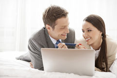 Playful business couple with laptop in hotel room Stock Photos