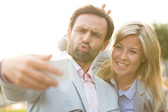 Playful business couple taking selfie outdoors on sunny day Stock Photos