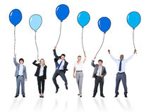 Playful Business People Holding Multicolored Balloons.  Stock Photo