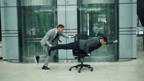 Playful business people are having fun in office lobby riding chair and playing racing game on rolling armchair. Playful business people in suits are having fun stock video footage
