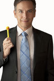 Playful Businessman Holds Duck Pen. A close-up shot of a businessman holding a yellow duck pen up with a playful expression on his face royalty free stock photography