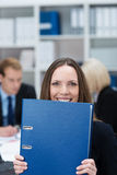 Playful businesswoman holding a large folder Stock Photography