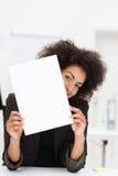 Playful businesswoman peeking around paper Stock Photos
