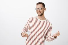 Playful carefree caucasian guy with bristle in black trendy glasses, closing eyes and smiling joyfully, mimicking stock images